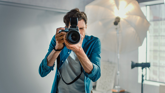 In the Photo Studio with Professional Equipment: Portrait of the Famous Photographer Holding State of the Art Camera Taking Pictures with Softboxes Flashing in Background.