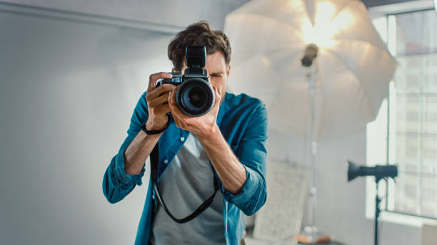 Im Fotostudio mit professioneller Ausstattung: Portrait of the Famous Photographer Holding State of the Art Camera Taking Pictures with Softboxes Flashing in Background. – Foto