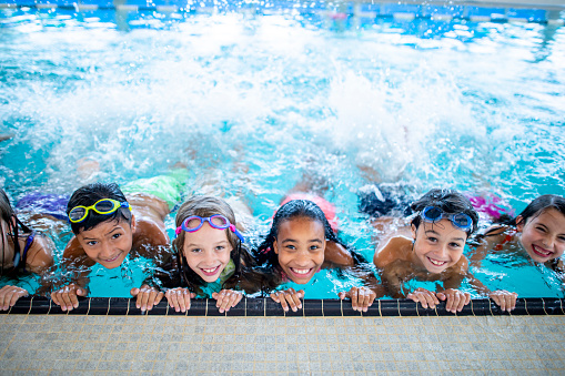 A group of elementary school children are at the pool. They are smiling and posing for the camera.