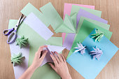 Children make Christmas trees from colored paper, origami.