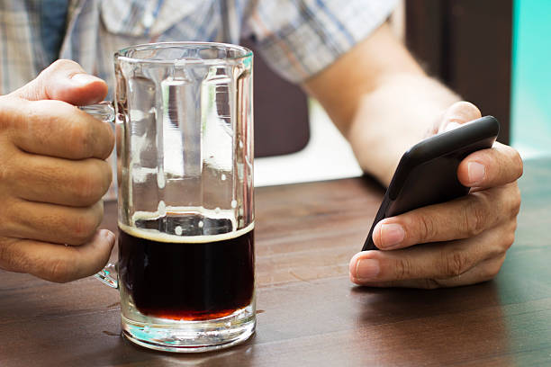 In the pub Close-up of male hands with mug of beer and smart phone. old man working in a pub stock pictures, royalty-free photos & images
