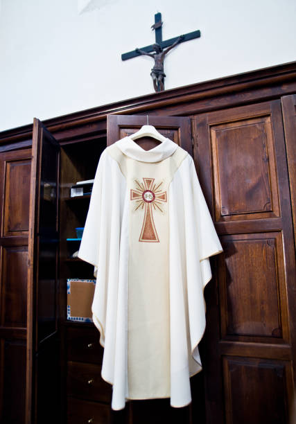 in the sacristy the cassock ready for Holy Mass clothing ready for Holy Mass hanging in the sacristy of the priest clergy stock pictures, royalty-free photos & images