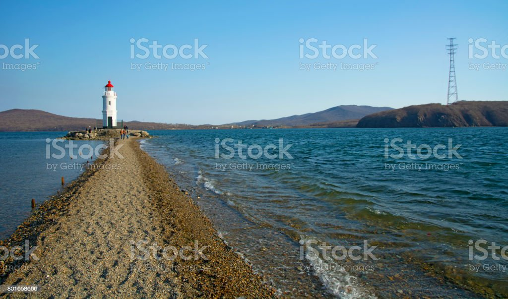in the sea filled the road to the lighthouse, in the middle of the Sea Beach line passes stock photo