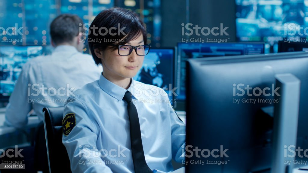 In the Security Command Center Officer at His Workstation Monitors Multiple Screens for Unlawful Infiltration. They're Guarding Important International Logistics Facility. stock photo