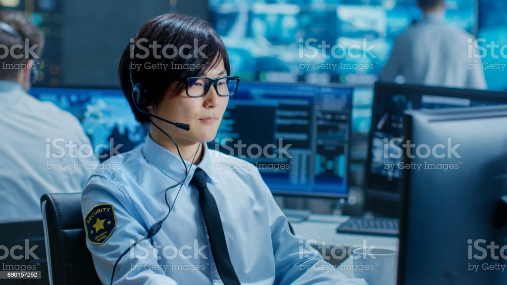 In the Security Command Center Officer at His Workstation Monitors Screens and Communicates with Patrols through Headset. He is Part of the Surveillance Team. stock photo