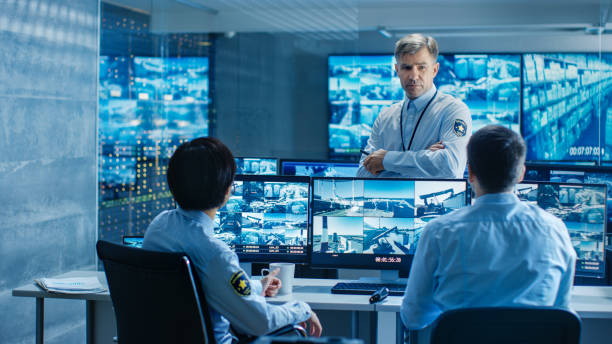 In the Security Control Room Chief Surveillance Officer Holds a Briefing for Two of His Subordinates. Multiple Screens Show that They Guard Object of International Importance. stock photo