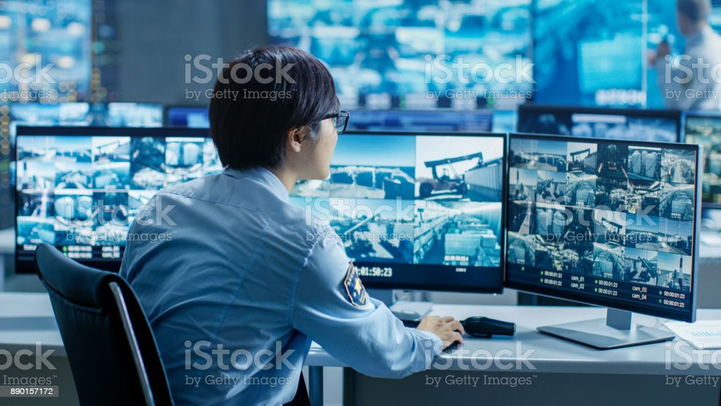 In the Security Control Room Officer Monitors Multiple Screens for Suspicious Activities. He's Surrounded by Monitors and Guards Facility of National Importance. stock photo