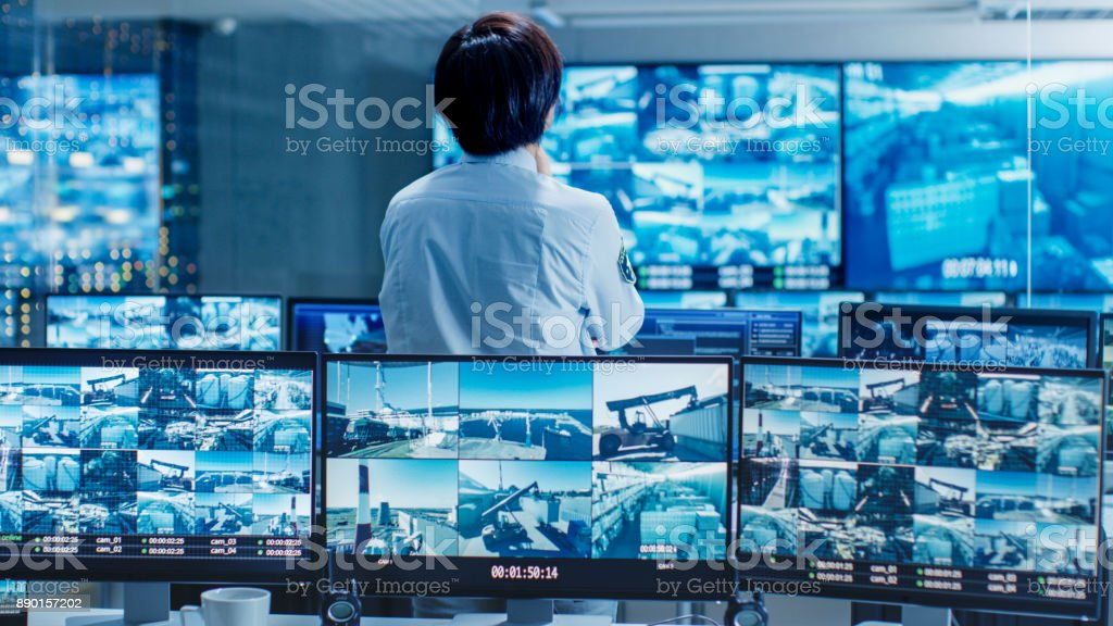 In the Security Control Room Officer Monitors Multiple Screens for Suspicious Activities. He Guards Internationally Important Logistics Facility. stock photo