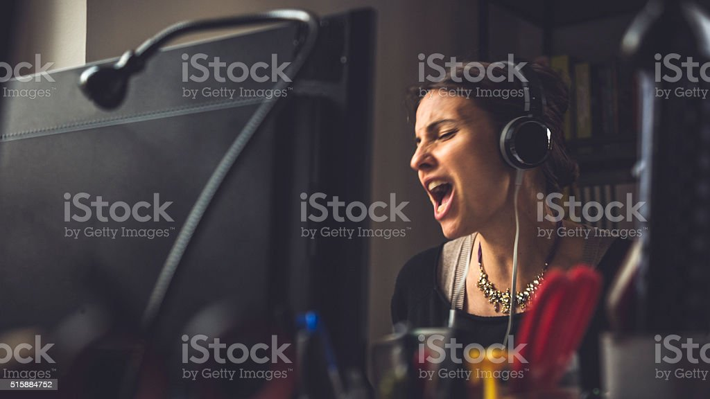 In the small business office: woman singing at work stock photo