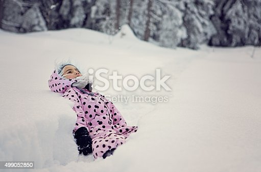 Little girl is exhausted and is lay down on the path in the snowy wood.