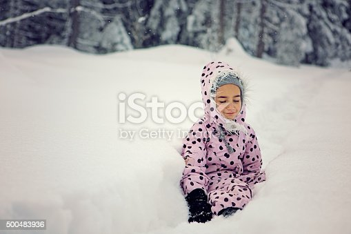 Little girl is exhausted and is sitting down on the path in the snowy wood.