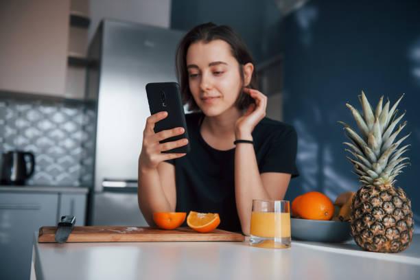 In den sozialen Medien. Mädchen in der modernen Küche zu Hause an ihrem Wochenende in der Morgenzeit – Foto