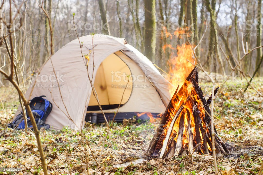 In the spring forest a tent with a fire