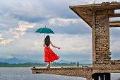 woman fashion dress walking on the retro old cottage house in the lake, holding umbrella under raining season\