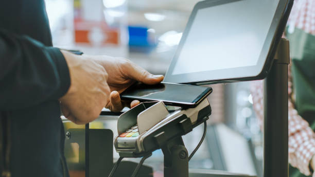 in the supermarket close-up footage of the man paying with smartphone at the checkout counter. using modern and convenient wireless nfc paying system in big mall. - contactless payment stock pictures, royalty-free photos & images