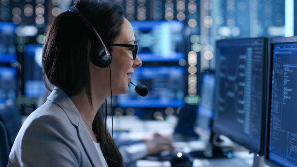 In the System Control Center Woman working in a Technical Support Team Gives Instructions with the Help of the Headsets. Possible Air Traffic/ Power Plant/ Security Room Theme. stock photo