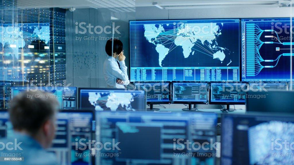 En el sistema de Control sala jefe ingeniero piensa mientras permanente antes de gran pantalla con mapa interactivo en el. Centro de datos está completo de monitores mostrando gráficos. - foto de stock