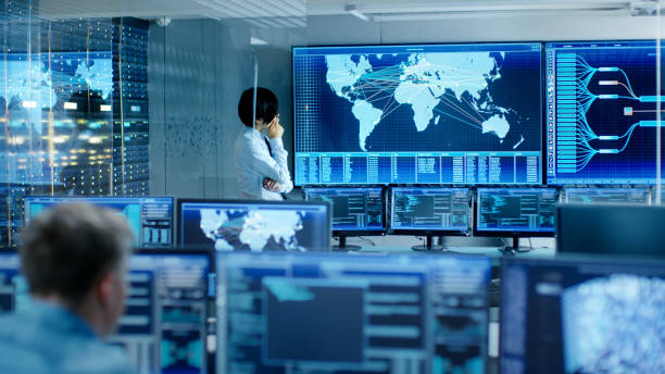In the System Control Room Chief Engineer Thinks While Standing Before Big Screen with Interactive Map on it. Data Center is Full of Monitors Showing Graphics. stock photo