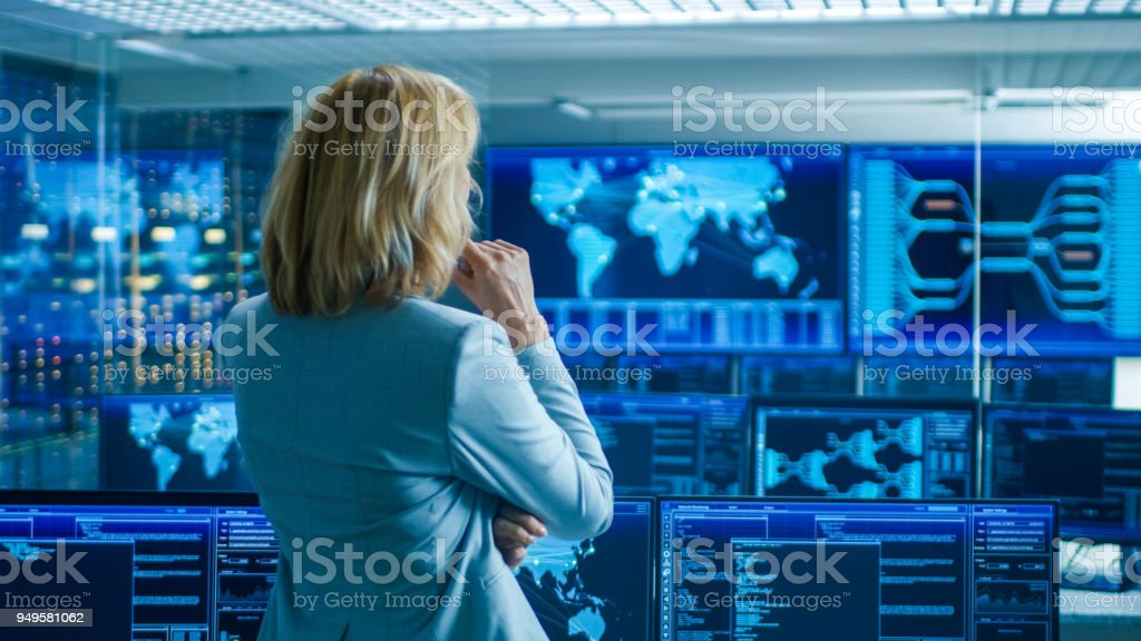 In the System Control Room Female Head of the Department Crosses Arms and Thinks Standing with Her Back to the Camera. In the Background Multiple Screens Showing Interactive Data. royalty-free stock photo