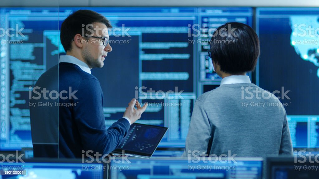 In the System Control Room IT Specialist and Project Engineer Have Discussion while Holding Laptop, they're surrounded by Multiple Monitors with Graphics. They Work in a Data Center on Data Mining, AI and Neural Networking. - Royalty-free Administrator Stock Photo