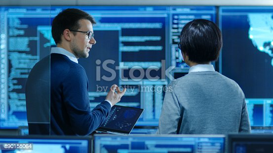 istock In the System Control Room IT Specialist and Project Engineer Have Discussion while Holding Laptop, they're surrounded by Multiple Monitors with Graphics. They Work in a Data Center on Data Mining, AI and Neural Networking. 890155064