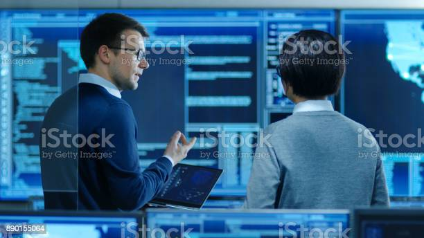In The System Control Room It Specialist And Project Engineer Have Discussion While Holding Laptop Theyre Surrounded By Multiple Monitors With Graphics They Work In A Data Center On Data Mining Ai And Neural Networking Stock Photo - Download Image Now