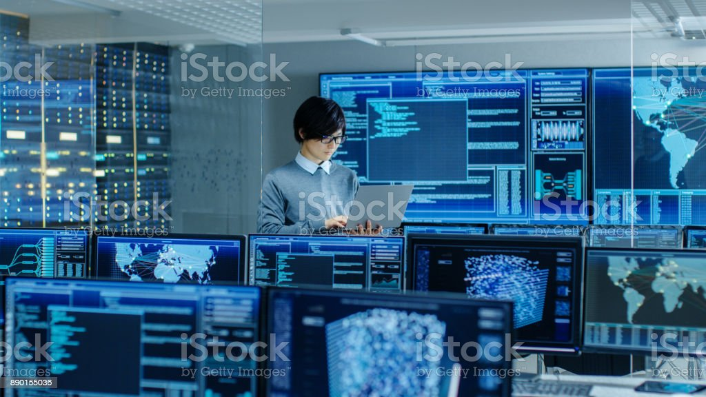 In the System Control Room IT Technician Holds and Works on a Laptop, in Background Multiple Displays with Graphics. Facility Works on Artificial Intelligence, Big Data Mining, Neural Network, Surveillance Project. stock photo