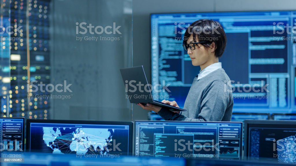 In the System Control Room IT Technician Works on a Laptop, in Background Multiple Displays with Graphics. Facility Works on Artificial Intelligence, Big Data Mining, Neural Network, Surveillance Project. stock photo