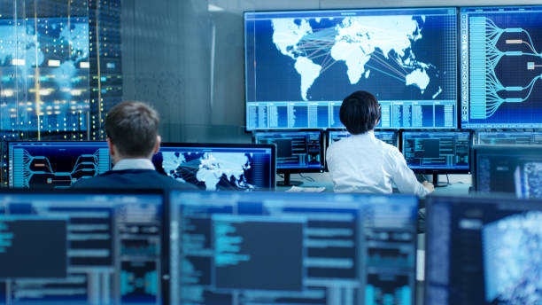 In the System Control Room Operator and Administrator Sitting at Their Workstations with Multiple Displays Showing Graphics and Logistics Information. stock photo