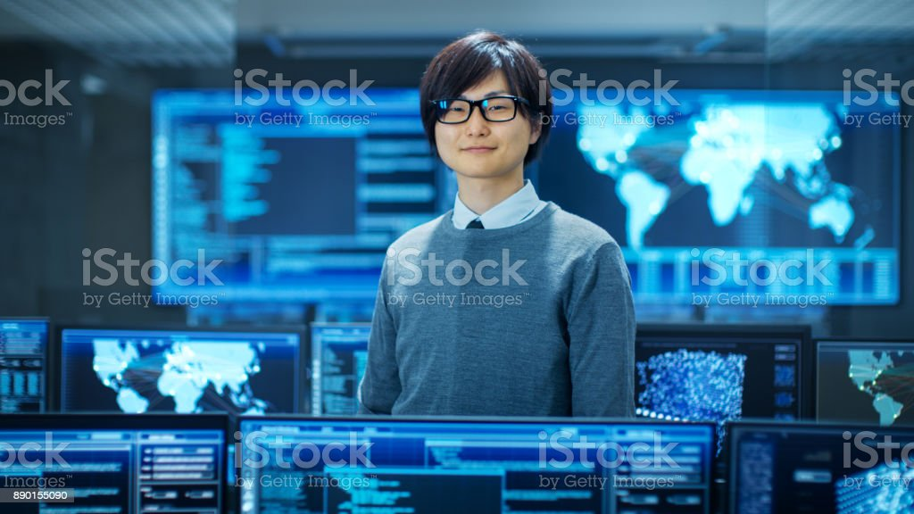 In the System Control Room Smart Engineer Smiles and Makes Thinking Gesture. High-Tech Facility Has Multiple Monitors with Graphics. stock photo