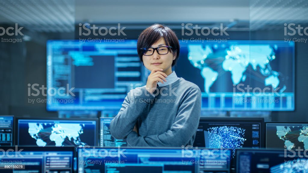 In the System Control Room Smart Engineer Turns and Makes Thinking Gesture. High-Tech Facility Has Multiple Monitors with Graphics. stock photo