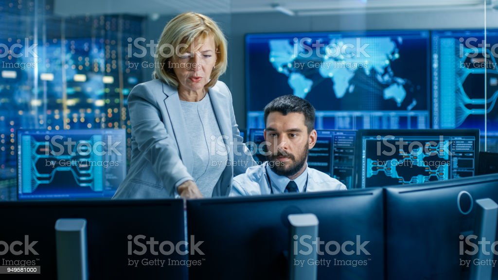 In the System Monitoring Room Senior Supervisor Controls Work of the Operator. They're Surrounded by Monitors Showing Relevant Technical Data. In the System Monitoring Room Senior Supervisor Controls Work of the Operator. They're Surrounded by Monitors Showing Relevant Technical Data. Adult Stock Photo