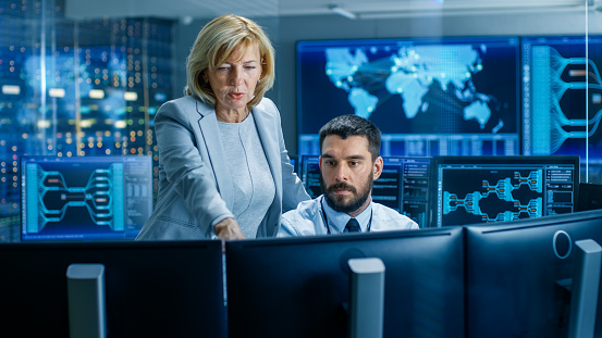 In The System Monitoring Room Senior Supervisor Controls Work Of The Operator Theyre Surrounded By Monitors Showing Relevant Technical Data Stock Photo - Download Image Now