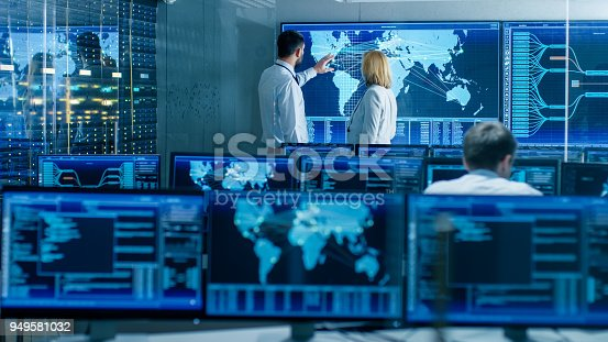 In the System Monitoring Room Two Senior Operators Work on a Big Interactive Map. Facility is Full of Screens Showing Technical Data.