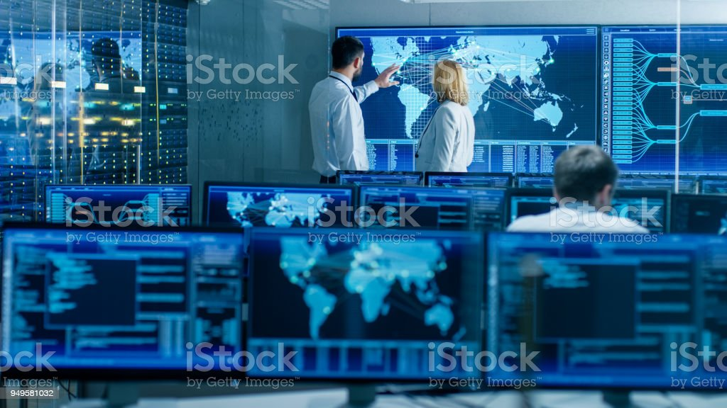 In the System Monitoring Room Two Senior Operators Work on a Big Interactive Map. Facility is Full of Screens Showing Technical Data. stock photo