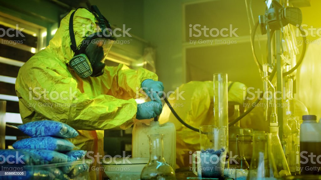 In the Underground Drug Laboratory Two Clandestine Chemists Wearing Protective Masks and Coveralls Use Hosepipe For Drug Distillation. They Cook Synthesised Drugs in the Abandoned Building. stock photo