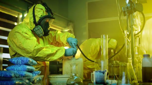im unterirdischen medikament labor verwenden zwei heimliche chemiker tragen von schutzmasken und overalls schlauch für droge-destillation. sie kochen synthetisierte drogen in das verlassene gebäude. - dokumentation stock-fotos und bilder