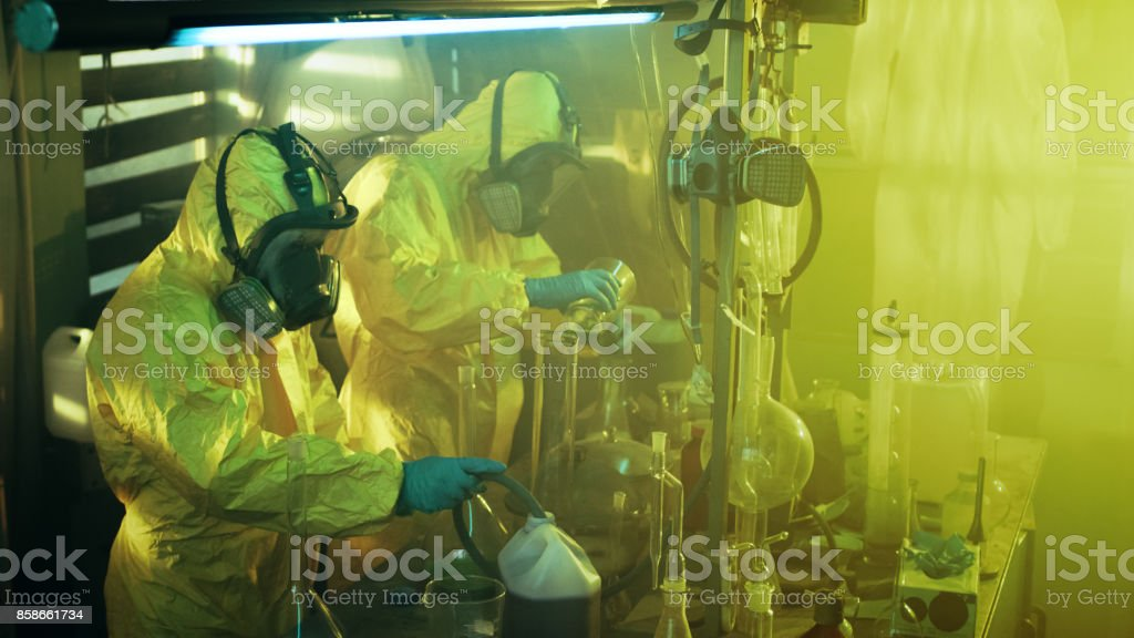 En el laboratorio subterráneo de dos químicos clandestinos usar máscaras y batas protectoras cocinan drogas. Trabajan con vasos, destilación de vidrio, frascos y manguera. Concepto de crimen verdadero. - foto de stock