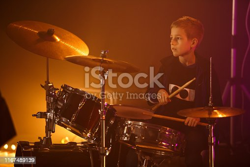 Teenage boy sitting behind drums and concentrating while playing rock music. He is on the stage at the concert and is looking away.