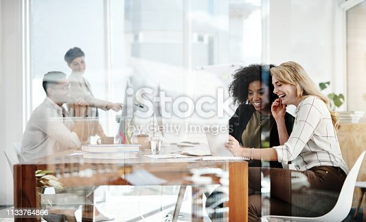 Shot of two businesswomen working on a digital tablet with their colleagues in the background in an office