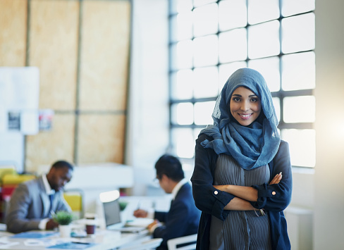 Portrait of a muslim businesswoman standing in an office with her colleagues in the background