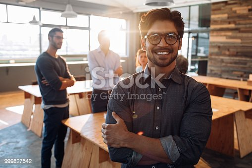 Shot of a young businessman standing in an office with his colleagues in the background