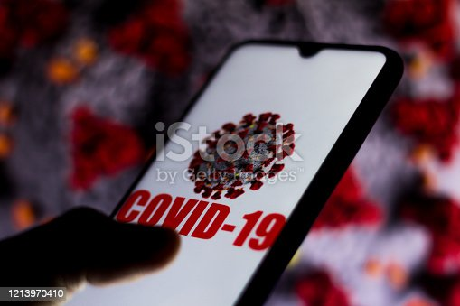 istock In this photo illustration the Covid-19 virus is displayed on the smartphone screen. Coronavirus appears in the background. 1213970410