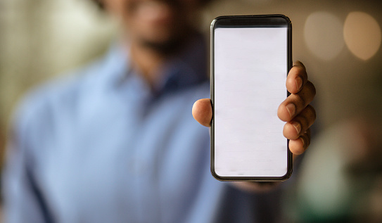 Time when it is impossible without technology. Business man holding smart phone. Focus is on hand.