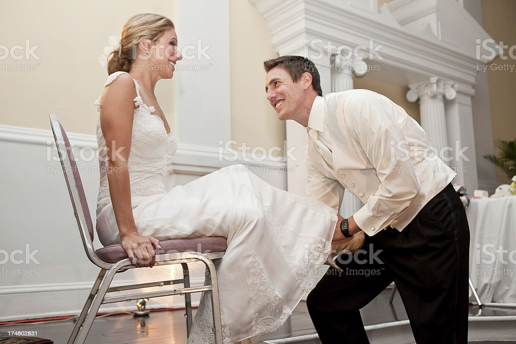 In Tradition Groom is Removing the Garter from his Bride royalty-free stock photo