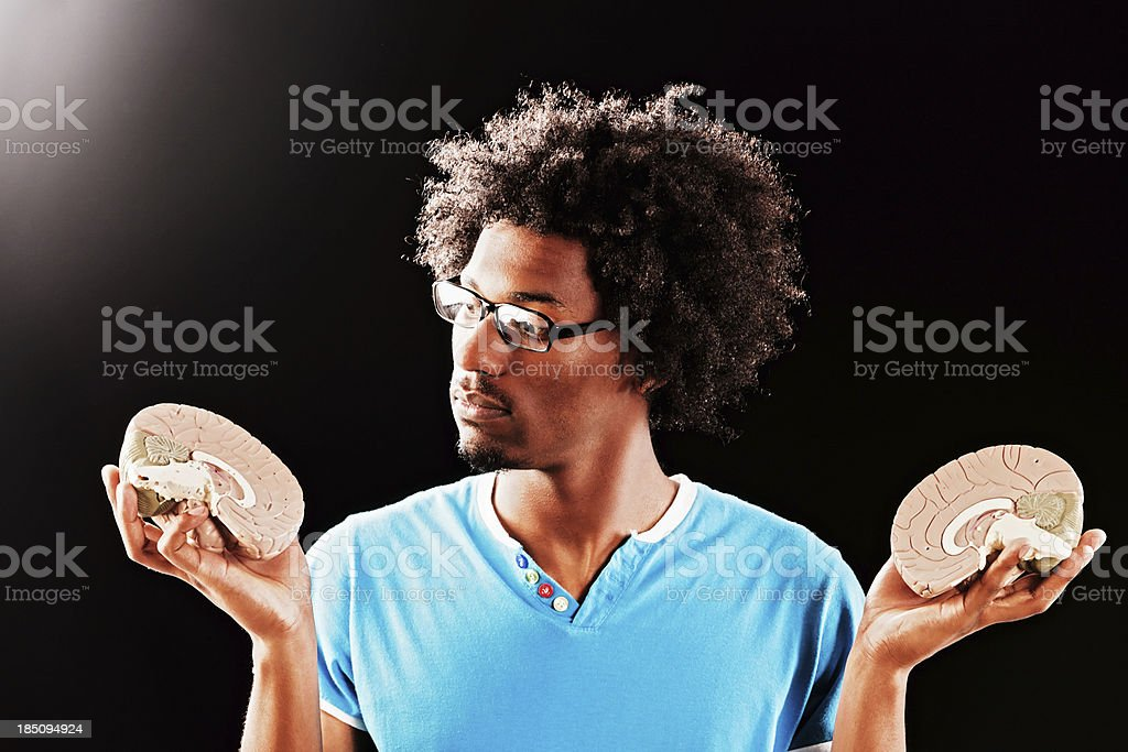 In two minds: young geek with model brain halves royalty-free stock photo