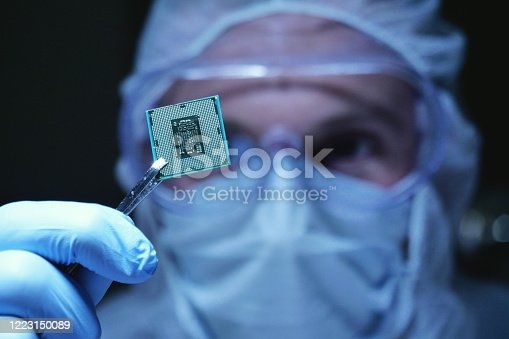 in Ultra Modern Electronic Manufacturing Factory Design Engineer in Sterile Coverall Holds Microchip with symbols in futuristic holography. artificial intelligence, future of robots.