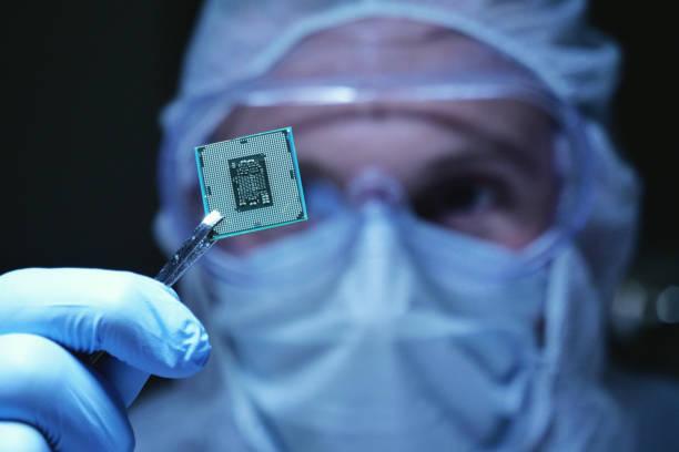 滅菌カバーオールの超近代的な電子製造工場設計エンジニアでは、未来的なホログラフィーのシンボルとマイクロチップを保持しています。 - 半導体 ストックフォトと画像