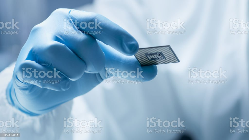 In Ultra Modern Electronic Manufacturing Factory Design Engineer in Sterile Coverall Holds Microchip with Gloves and Examines it. stock photo