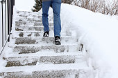 In winter it is dangerous to walk up a snow-covered staircase. A man walks up a staircase in winter